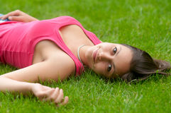 Beautiful smiling girl lying on the grass Stock Photo