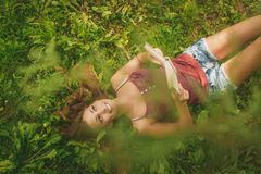 Daydream. Beautiful smiling girl lying in grass, holding book and thinking. Top view Stock Photos