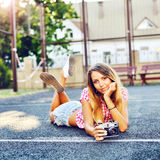 Beautiful smiling girl lying on a ground with old retro camera Royalty Free Stock Image