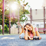 Beautiful smiling girl lying on a ground with old retro camera Stock Photography