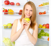 Smiling girl near the refrigerator Royalty Free Stock Image