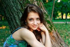 Beautiful smiling girl near the tree in the park Stock Images