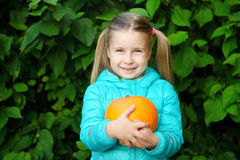 Beautiful smiling girl outdoors holding little pumpkin. Beautiful smiling girl holding little pumpkin Stock Image