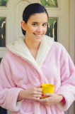 Beautiful smiling girl in pajamas drinking coffee outdoor. Beautiful smiling girl in night gown drinking coffee in front of her house early in the morning Stock Images