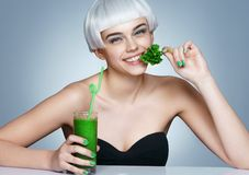 Beautiful smiling girl with parsley and green detox cocktail. Royalty Free Stock Photo