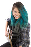 Beautiful smiling girl playing guitar. On a white background. Pierced, turquoise haired and dressing up a plaid shirt and black jeans Royalty Free Stock Image