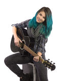 Beautiful smiling girl playing guitar. On a white background. Pierced, turquoise haired and dressing up a plaid shirt and black jeans Stock Photography