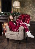 A beautiful smiling girl in red Christmas home clothes pajamas and white home boots sits in a chair against the background of th. E Christmas tree and fireplace stock image
