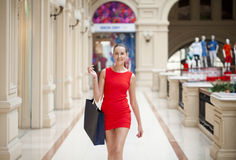 Beautiful smiling girl in a red dress, holding shopping bags Stock Photos