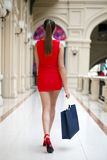 Beautiful smiling girl in a red dress, holding shopping bags Royalty Free Stock Photography