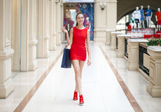 Beautiful smiling girl in a red dress, holding shopping bags Stock Photo