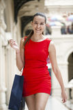 Beautiful smiling girl in a red dress, holding shopping bags Royalty Free Stock Photos