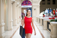 Beautiful smiling girl in a red dress, holding shopping bags Royalty Free Stock Photo