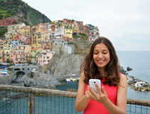 Beautiful smiling girl with red dress sending a message by cell phone in Manarola, Cinque Terre. Young woman with italian landscap. E with colorful houses on royalty free stock image