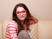 Beautiful smiling girl in red glasses sitting Royalty Free Stock Image