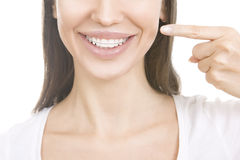 Beautiful smiling girl with retainer for teeth pointing at her s Stock Image