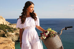 Beautiful smiling girl riding a bicycle along the sea coast. Fashion outdoor photo of beautiful smiling girl with dark hair in elegant white dress riding a Royalty Free Stock Photo