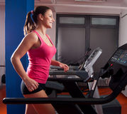 Beautiful smiling girl running on treadmill. In the gym Stock Photo