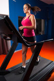 Beautiful smiling girl running on treadmill in the modern gym Royalty Free Stock Photo