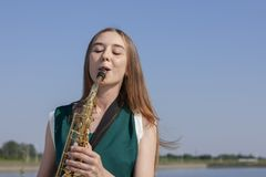 Beautiful smiling girl with saxophone. Young beautiful saxophonist with saxophone - outdoor in nature stock photos