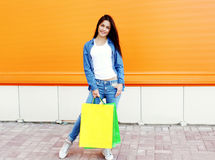 Beautiful smiling girl with shopping bags in jeans clothes. Over orange wall Stock Images