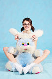 Beautiful smiling girl sits with a soft toy rabbit. Royalty Free Stock Images