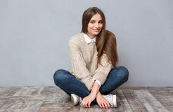 Beautiful smiling girl sitting on the floor with legs crossed Royalty Free Stock Photo