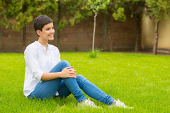 Beautiful smiling girl sitting on the grass of home garden Royalty Free Stock Photos