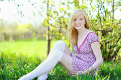 Beautiful smiling girl sitting on the grass in a park Stock Photo