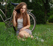 Beautiful smiling girl sitting next to bike on fresh grass with her eyes half closed Stock Images