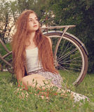 Beautiful smiling girl sitting next to bike on fresh grass with her face looking up toned image Royalty Free Stock Images