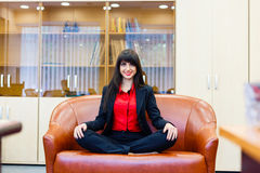 Beautiful smiling girl sitting on sofa in the lotus position Royalty Free Stock Images