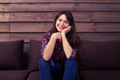 A beautiful smiling girl sitting on the sofa royalty free stock photography