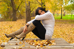 Beautiful smiling girl sitting on the table with leaves Royalty Free Stock Photos
