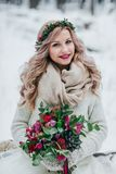 Beautiful smiling girl of Slavic appearance with a wreath of wildflowers holds a bouquet in winter background. Royalty Free Stock Photos