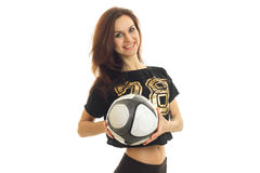 Beautiful smiling girl in a sports shirt holds the ball and looks into a camera Stock Image
