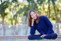 Beautiful smiling girl with sportswear is sitting and relaxing i Royalty Free Stock Photo