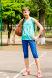 Beautiful smiling girl standing with a basketball in outdoor basketball court Stock Photo