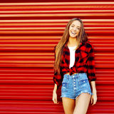Beautiful smiling girl standing near red wall - copy space Royalty Free Stock Photo