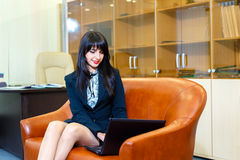 Beautiful smiling girl in a suit sitting in office on the cou Stock Photo