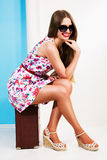 Beautiful smiling girl in a summer dress sits on a suitcase Stock Photos