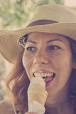 Beautiful smiling girl in a summer hat eating ice cream cone Stock Photography