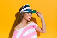 Beautiful Smiling Girl In Sun Visor Cap. Smiling young woman in pink stripped shirt holding sun visor cap and looking away. Studio portrait on yellow background Stock Photo