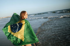 Beautiful smiling girl in sunglasses with Brazilian flag on beac Stock Photo