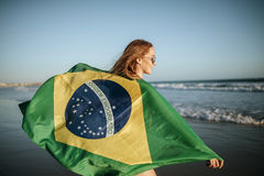 Beautiful smiling girl in sunglasses with Brazilian flag on beac Stock Photography