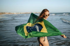 Beautiful smiling girl in sunglasses with Brazilian flag on beac Royalty Free Stock Photos