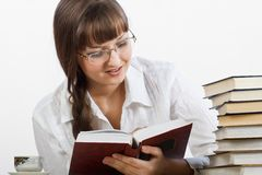 Beautiful Smiling girl thoughtfully reading a book Stock Image