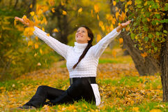 Beautiful smiling girl throwing dry leaves in the air Royalty Free Stock Photo