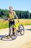 Beautiful smiling girl walks with bicycle Royalty Free Stock Photography