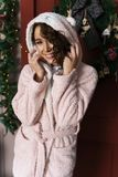 A beautiful smiling girl in a warm fluffy robe, dressed in a hoo royalty free stock photos